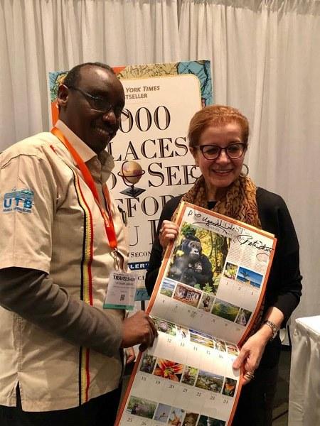 Patricia Schultz and UTB's Stephen Asiimwe display the calendar featuring Destination Uganda